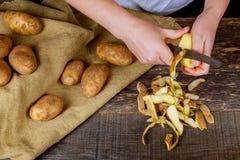 妇女细节递剥与厨房削皮器,食物配制概念的新鲜的黄色土豆 免版税库存图片
