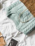 妇女编织了在一个纸袋的蓝色毛线衣和有耳机的一个智能手机在轻的背景,顶视图 妇女` s衣物 免版税图库摄影