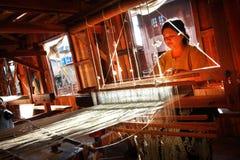 妇女编织丝织物 图库摄影