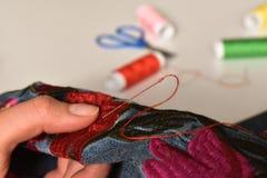 妇女缝合与针,并且红色螺纹和在背景中是某一针线包 免版税库存照片