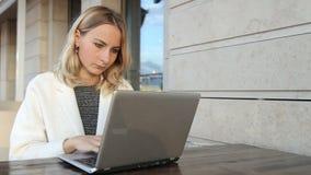 妇女网上购物通过在咖啡馆的膝上型计算机 股票录像