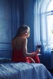 妇女美丽的剪影坐床和饮用的a 免版税库存照片