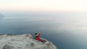 妇女美丽的景色做着瑜伽nantasana,在山的边斜倚的腿推力有在日落天线的海视图 股票视频