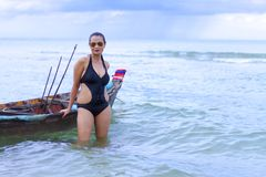 妇女美丽的黑比基尼泳装和小船在海滩 免版税库存照片