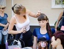 妇女美发师做女孩的一种发型在城市党 库存照片