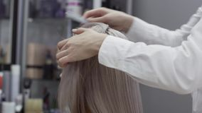 妇女美发师的手分离客户女孩的头发子线 股票视频