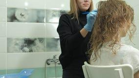 妇女美发师着色师在卫生间在年轻女人的头发上在家把油漆放,应用与刷子的油漆 股票录像