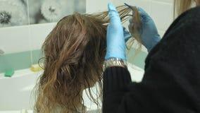妇女美发师着色师在卫生间在年轻女人的头发上在家把油漆放,应用与刷子的油漆 股票视频
