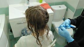 妇女美发师着色师在卫生间在年轻女人的头发上在家把油漆放,应用与刷子的油漆 影视素材