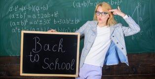 妇女老师拿着黑板回到在黑板背景的学校题字 申请引起轰动教育 库存图片