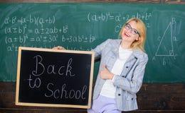 妇女老师拿着黑板回到在黑板背景的学校题字 申请引起轰动教育 免版税图库摄影