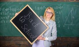 妇女老师正式衣服拿着黑板题字回到学校 夫人教育家在教室为新的学校做准备 免版税库存照片