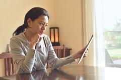 妇女考虑购买通过互联网在家坐椅子 免版税库存照片