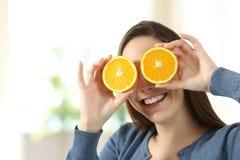 妇女耍笑与两个半橙色切片 免版税库存照片