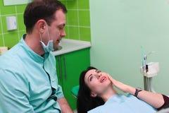 妇女耐心谈话与男性牙医和诉说牙痛在牙齿诊所办公室 库存照片