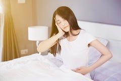 妇女胃痛和头疼在她的床上在卧室 图库摄影