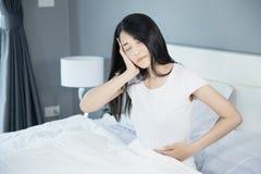 妇女胃痛和头疼在她的床上在卧室 库存照片