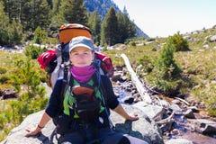妇女背包徒步旅行者坐的岩石 免版税库存照片