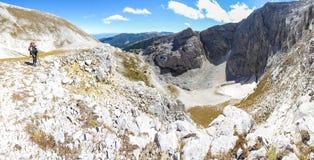 妇女背包徒步旅行者常设山边缘全景 免版税库存图片