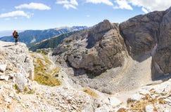 妇女背包徒步旅行者常设山边缘全景 库存图片