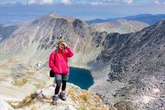 妇女背包徒步旅行者常设山 免版税库存照片