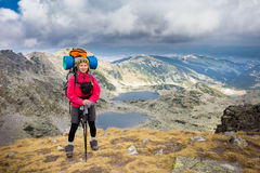 妇女背包徒步旅行者常设山 免版税图库摄影