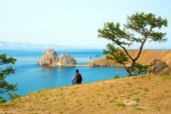 妇女背包徒步旅行者看Shamanka岩石,在奥尔洪岛的海角Burhan 贝加尔湖湖俄国 免版税图库摄影