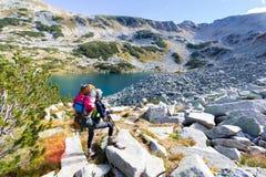 妇女背包徒步旅行者站立的下个山湖 库存照片