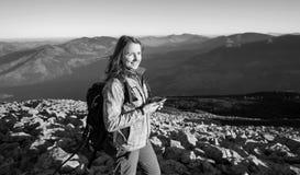 妇女背包徒步旅行者画象在山的岩石上面的 库存照片