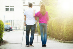 妇女背面图有她的残疾丈夫的 免版税库存图片
