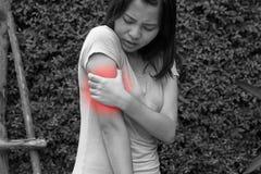 妇女胳膊、肩膀或者关节痛在庭院,黑白骗局里 库存图片
