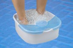 妇女脚在一个振动的脚按摩器的脚浴放松在蓝色backround 库存照片