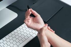 妇女腕子胳膊痛苦长的用途笔老鼠工作 办公室综合症状医疗保健和医学概念 库存图片