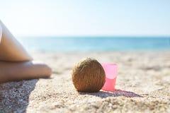 妇女腿、椰子和玫瑰色塑料杯子在沙子在海滩在明亮的晴朗的早晨 库存照片
