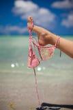 妇女腿举行在异乎寻常隔绝的桃红色胸罩 免版税库存图片