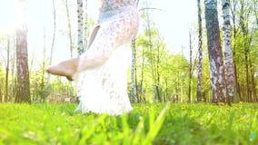 妇女腿低角度射击赤足跳舞在与透镜火光的绿草的 股票视频