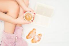 妇女腿特写镜头有喝咖啡和读一本好书的蓬松拖鞋的 免版税图库摄影