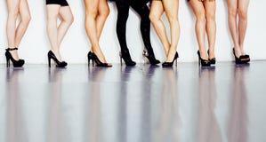 妇女腿的不同的类型对在hight的停顿在白色背景和地板隔绝的黑鞋子,变化人 库存照片