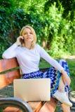 妇女膝上型计算机在公园享用绿色自然和新鲜空气 梦想的女孩利用网上购物 女孩坐长凳 库存照片