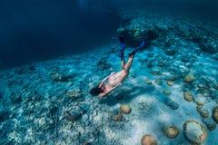 妇女自由潜水者游泳在水面下在热带海洋 免版税库存图片