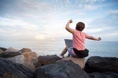 妇女自由职业者在舒展在天空的桃红色衬衣 免版税库存照片