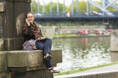 妇女自由职业者坐河的石堤防有膝上型计算机的和谈话在电话 免版税库存照片