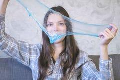 妇女舒展蓝色软泥坐教练和使用 看通过软泥 库存图片