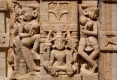 妇女舞蹈在Lakshmi女神附近的在传统印度石寺庙墙壁上  免版税库存图片