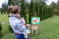 妇女艺术家在手中站立与刷子在画架,看和f附近 免版税库存图片