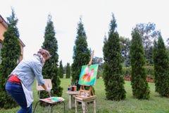 妇女艺术家在手中站立与刷子在画架,看和f附近 图库摄影