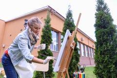 妇女艺术家在手中站立与刷子在画架,看和f附近 免版税图库摄影