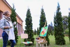 妇女艺术家在手中站立与刷子在画架,看和f附近 库存图片