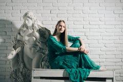 妇女艺术家梦想和认为在石膏雕塑在关于白色砖墙背景的车间 艺术和雕塑 艺术 免版税库存照片