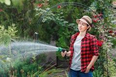 妇女花匠浇灌的庭院 库存图片